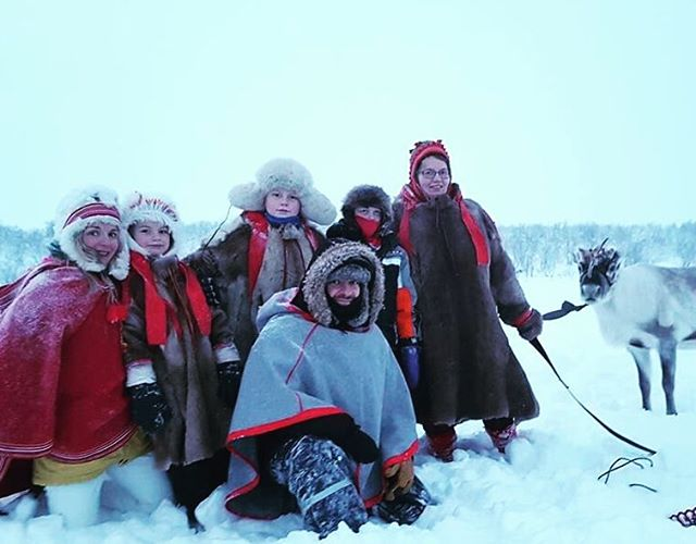 Happy travelers visiting reindeer stock in Tundra with a local Sami family in the Northern Norway